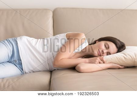 Pretty young woman lying on comfortable sofa with clothed eyes and smiling. Adorable lady takes short nap during day to increase productivity. Teen girl relaxing at home. Biological rhythms concept