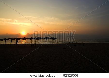 silhouettes of man on beach at sunrise