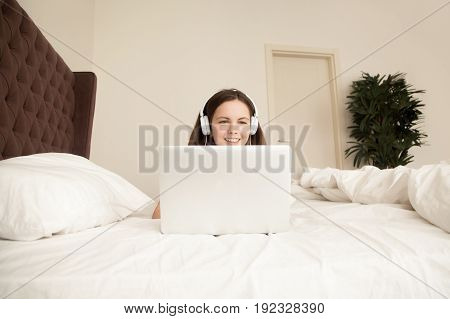 Happy young woman in headphones lying in front of laptop on cozy bed with white sheets. Teenager girl buying music online, learns language course, plays game, talks with friends via video conference