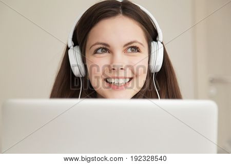 Close up portrait of beautiful smiling woman in headphones in front of laptop. Happy young lady listening to popular music with charming smile, studying foreign language with great pleasure