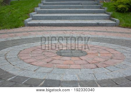 Granite tiles laid out in the form of a circle with an exit through the steps. Another meaning: when you walk around in a circle for a long time but there is still a way out