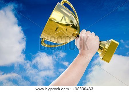 hand holding golden trophy with blue sky background