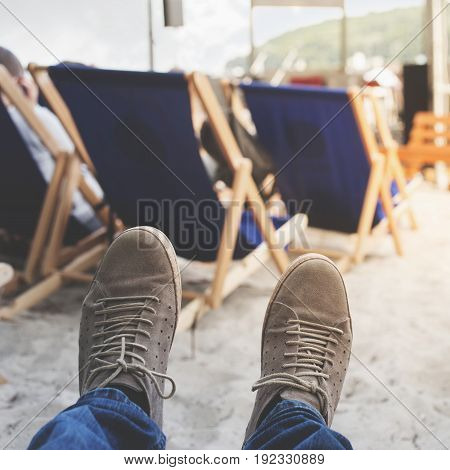 Men legs in sneakers on a background of deckchairs on the beach. Holiday background