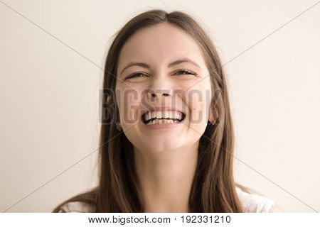 Headshot portrait of laughing young woman. Cheerful teen girl with happy facial expression looking at camera with toothy smile. Female positive emotion, comic situation concept. Close up. Front view