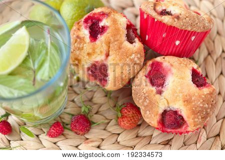 Fresh homemade delicious berry muffins and drink water with lime and mint leaves.