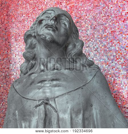 Jesus statue on mosaic wall background. Religious bronze sculpture