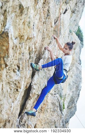 woman rock climber. rock climber climbs on a rocky wall. woman makes hard move