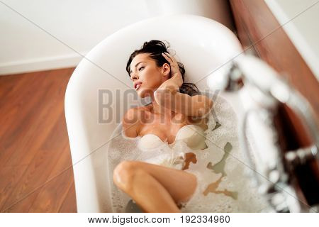 Beautiful and sensual young woman enjoying her time in bathtub