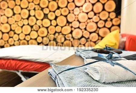 Tree trunks logs taped on a wall. House interior detail with a bed and towels