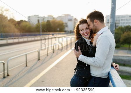 Happy couple cuddling while enjoying time spent together on bridge