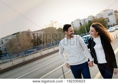 Happy young couple walking hand in hand together