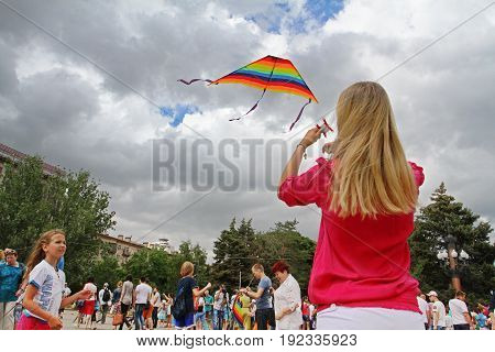 Volgograd Russia - June 12 2014: Woman launches a kite into the sky at the kite festival in Volgograd