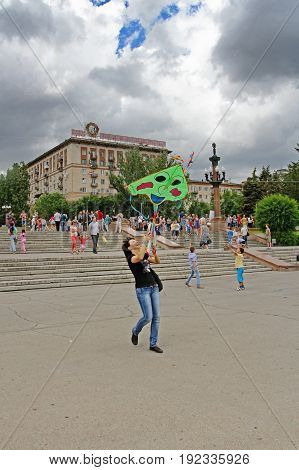 Volgograd Russia - June 12 2014: Smiling woman launches a kite into the sky at the kite festival in Volgograd