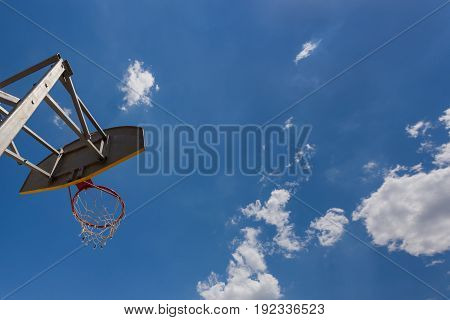 Street basketball ring against the sky and clouds. Backside.