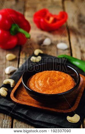 Red Bell pepper cashews sauce on a wood background
