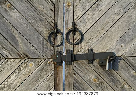 Metal handle and hasp with lock on wooden doors of the gate.