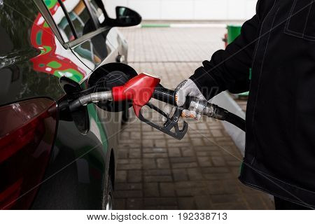 Close-up photo of hand holding fuel pump and refilling car at petrol station.