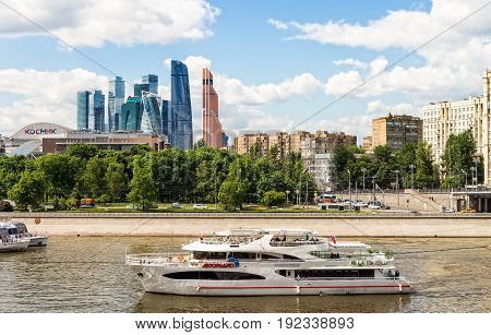 MOSCOW RUSSIA - JUNE 6 2017: Tourist boat on the Moscow river skyscrapers international business center