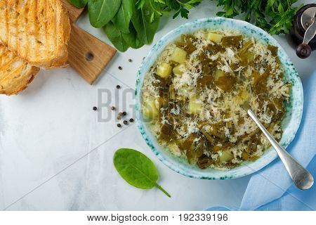 Simple vegetarian soup made of sorrel potatoes and beaten eggs on a light background. Selective focus.Top view.