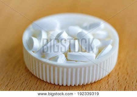 White Pills In A White Plastic Bottle Cap On The Table Closeup