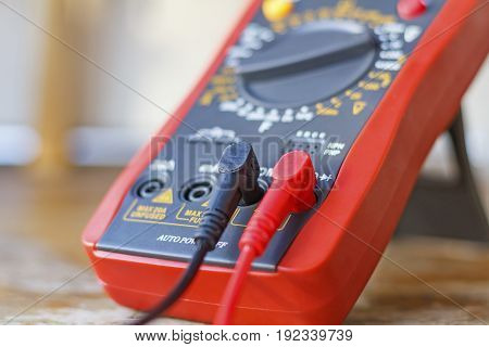 Digital Multimeter With Connected Probes On A Wooden Table