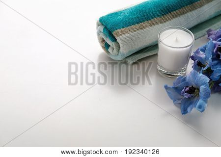 Towel, Blue Flower And Candle On White Table, Spa Concept