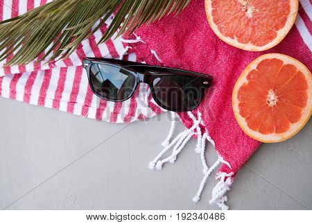 Close Up Summer Concept: Sunglasses, Towel, Grapefruit On A Gray Table, Top View