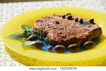 Tuna steak served with olives, basil and capper in yellow plate in blurry background