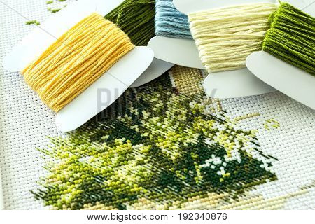 Cross-stitch embroidery on embroidery. Fragment of embroidery in natural colors. Selective focus. Close-up.