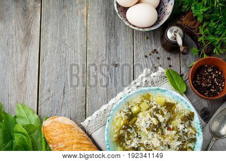 Simple vegetarian soup made of sorrel potatoes and beaten eggs on an old wooden background. Selective focus.Top view.