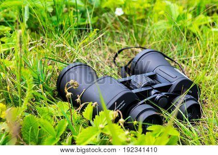 close-up of binoculars on green grass in adventure