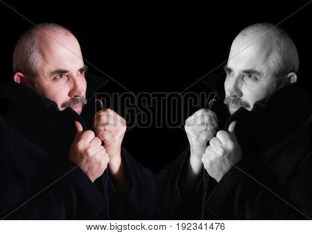 Symmetric (black and white vs color) Portrait of a Caucasian man wrapping himself up into a topcoat.