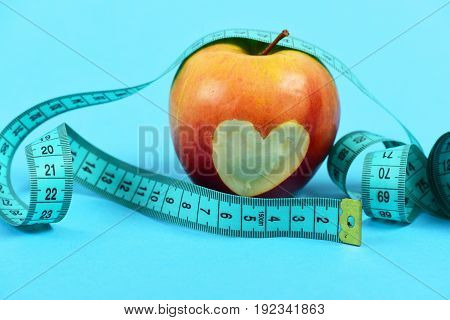 Apple of red color with bitten heart inside near cyan blue measuring tape isolated on turquoise background. Concept of health and love to your body
