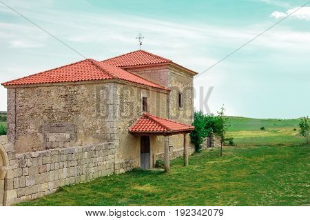 A photo of the Ermita de la Soledad, the hermitage in Campisabalos, a town in Spain with one of the world's purest air, with a view over a green hillside and a place for text