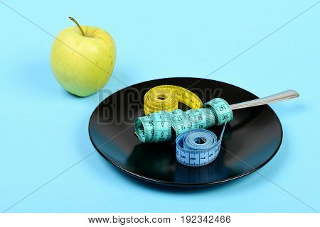 Apple In Green Color Next To Black Plate