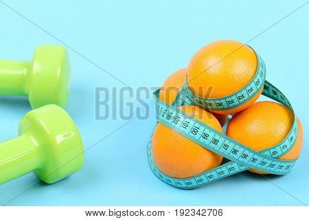 Pair Of Dumbbells Next To Oranges Wrapped With Measuring Tape