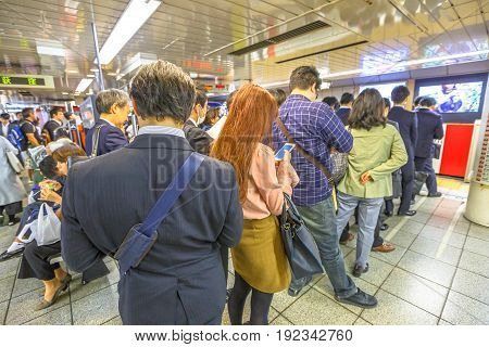 Tokyo, Japan - April 17, 2017: rush hour: crowd of people waiting the Marunouchi Line, subway line in Tokyo at Shinjuku Station. On maps and signboards, the line is shown in red and with the letter M.