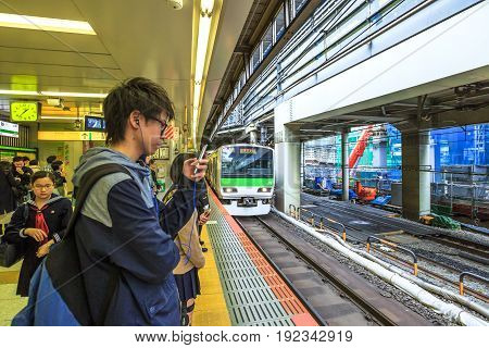 Tokyo, Japan - April 17, 2017: a boy looks at his smarth phone while waiting the Yamanote Line, the most important train line in Tokyo. The Yamanote is a JR line and a circular ring around city center