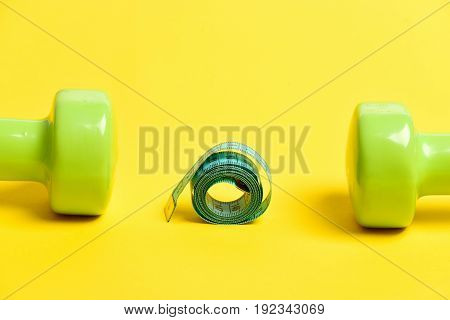 Roll of cyan measuring tape lying near pair of green lightweight dumbbells isolated on yellow background. Concept of sports slim shape and healthy lifestyle