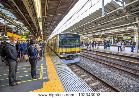 Tokyo, Japan - April 17, 2017: people waiting on tracks of Chuo Line local, for Akihabara, the yellow line of JR Line, a rail service that crosses east-west Tokyo downtown. Shinjuku Station.