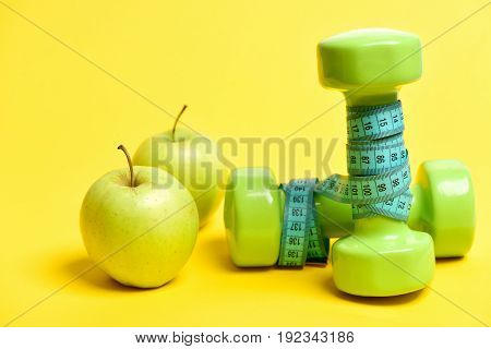 Pair Of Fresh Apples Near Green Dumbbells Wrapped With Tape