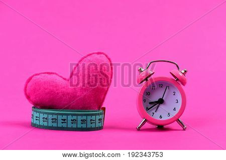 Roll of greenish blue measuring tape around heart next to alarm clock isolated on magenta pink background with copy space