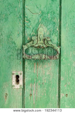 Closeup vintage antique Wooden door painted in worn green on a Country house door lock door handle and latch