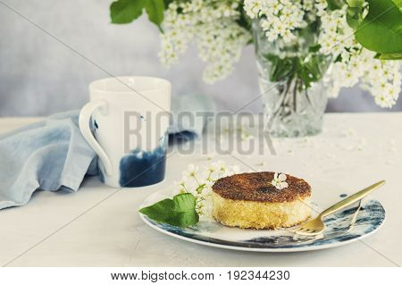 Piece of homemade semolina cake on plate, cup of tea and vase with blooming bird-cherry tree branches on grey concrete background. Spring summer breakfast. Selective focus. Toned image
