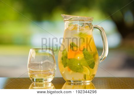 Jug of non-alcoholic drink and a glass on a table with a blurred background.