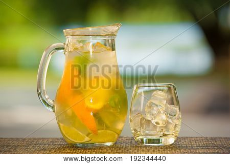 Jug of non-alcoholic drink and a glass of ice on a table with a blurred background.