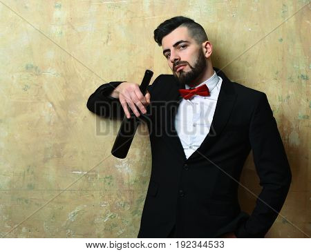Man with stylish beard and confident face expression in official suite holds bottle of wine on background of beige color wall of pub. Concept of leisure and party