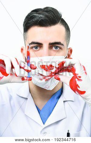 Doctor In Procedure Mask Holds Syringe