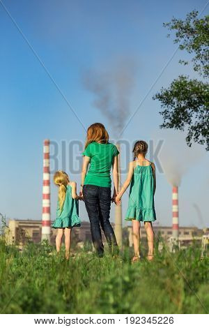 mother and daughter looking at the plant chimney-stacks polluting an air