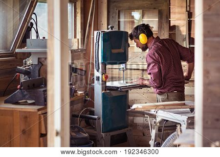 Male Carpenter Cutting Plank By Band Saw